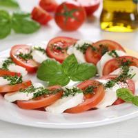 caprese sallad med ingredienser som tomater och mozzarellaost foto