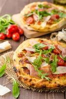 italiensk pizza med parmesanost, prosciutto och ruccola foto