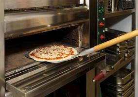 sätta pizza i ugnen foto
