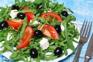 hälsosam sallad av ruccola, ost, tomat och oliver foto