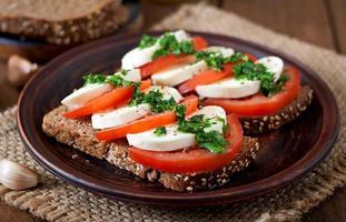 användbara smörgåsar med mozzarella, tomater och rågbröd foto