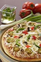 läcker pizza med grönsaker som omger den i miljö. foto