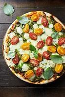 körsbärstomatpizza med mozzarella och basilikapesto foto