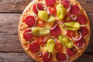 pizza med salami och peppar horisontell toppvy, rustik foto