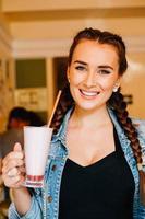 vacker flicka på ett café och dricka en milkshake foto