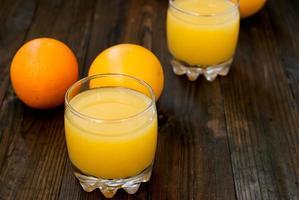 färsk apelsinjuice på träbord foto