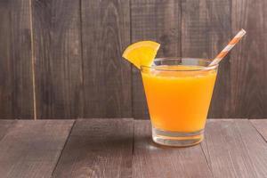 glas färsk apelsinjuice på träbord foto