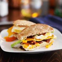två halvor av en frukostsmörgås på plattan foto