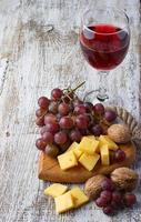 glas rött vin, druva och ost foto