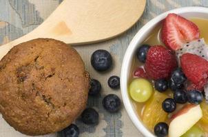 fruktsallad med kli muffin och träsked foto