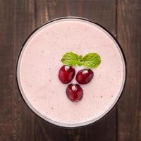 tranbärfruktsmoothie på träbakgrund, hälsosamt ätande. foto