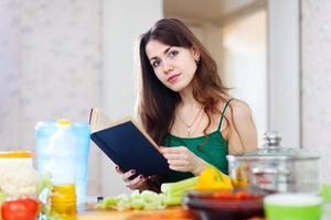 vacker kvinna läser kokbok för recept foto