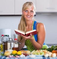 kvinna matlagning grönsaker med nytt recept foto