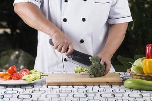 kock som skär broccoli foto
