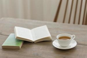 en enda kopp te på ett träbord med böcker foto