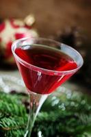röd julcoctail i ett martiniglas med grangrenar