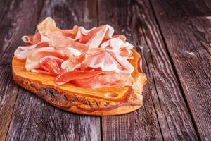 prosciutto serveras på en olivskärbräda foto