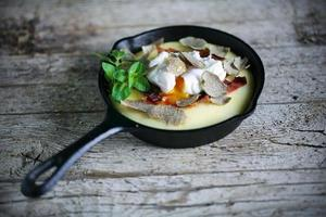 majsmjöl eller polenta med parmaskinka, pocherat ägg och tryffel foto