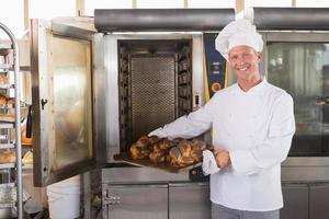 glad bagare som tar ut färskt bröd foto