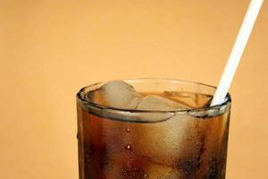 glas cola och is med ett sugrör foto