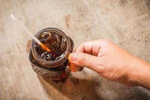 handinnehav av cola i glas med is på tabellen foto