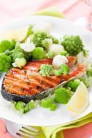 grillad lax med broccoli och blomkål på den vita plattan foto
