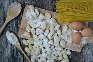 gnocchi på skärbräda och rustik träbakgrund foto