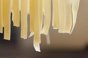 färsk hemlagad italiensk tagliatellepasta hängde på för torkning foto