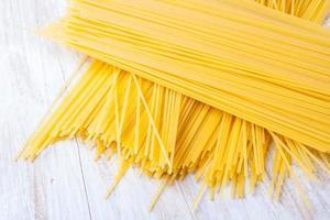 torr pasta på vitt träbord foto