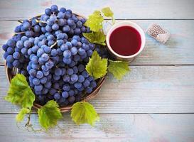 rött vin och druvor i vintage miljö foto