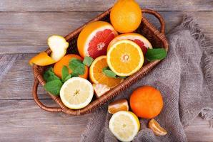 färska citrusfrukter med gröna blad på träbakgrund foto