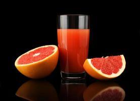 studio skott skivade tre grapefrukt med juice isolerad svart foto