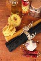 pastaspagetti, grönsaker och kryddor på bordet foto