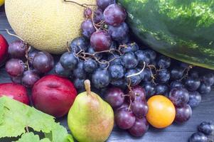olika frukter på det mörka träbordet foto