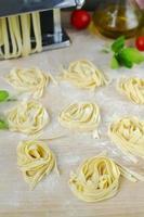 färsk hemlagad pasta maskin pasta, basilika, tomater på ett trä foto