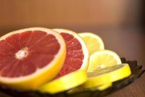 skivad grapefrukt och citron som ligger på plattan foto