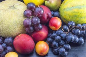 olika frukter på det mörka träbordet