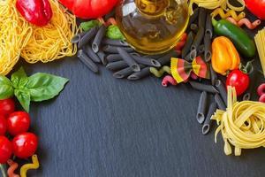 rå pasta med ingridients på svart tavla foto