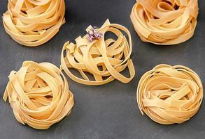 pasta och färsk rosmarinblomma på en svart skiffer foto
