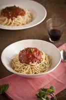 spagettimiddag med tomatsås och basilika på nära håll