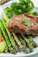 glaserade gröna sparris med grillad fläskkotlett foto