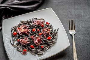 pasta med svart bläckfiskfärg och små bläckfiskar foto