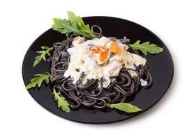svart pasta med skaldjursås foto