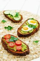 rågsmörgåsar och mosade avokado, ägg, tomater och gurkor foto