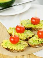 avokado med tomat på bröd foto