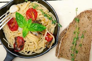spagettipasta med bakade körsbärstomater och basilika foto