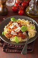 italiensk pastaspagetti bolognese med basilika på det rustika bordet