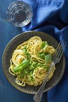 spagettipasta med pestosås över blått foto