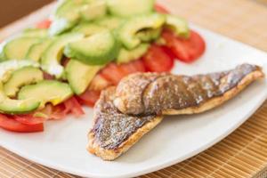 stekt förgylld havsbalk med tomater och avokado.