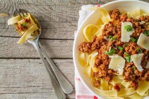 pasta bolognese i vit skål, rutig servett, ovanifrån foto